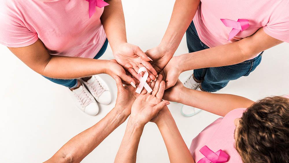 Quatro mulheres segurando juntas um laço rosa, símbolo do Outubro Rosa.
