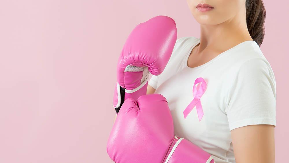 Mulher com luvas de boxe rosas e laço cor de rosa, símbolo da luta contra o câncer de mama, preso na lapela.