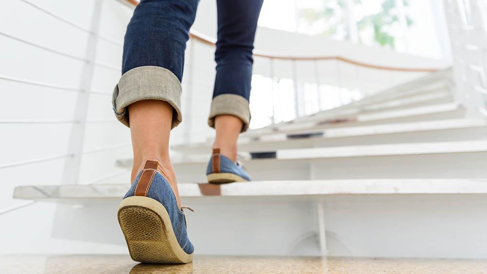Close em pernas de uma mulher subindo escadas.