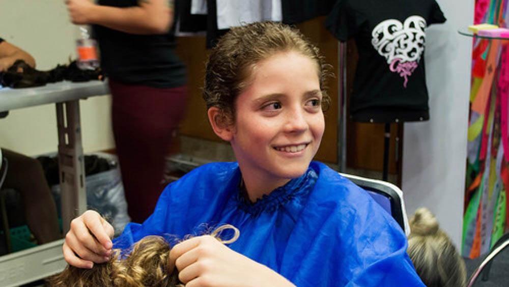 Menino sentado em cadeira de cabeleireiro após doar seu cabelo.