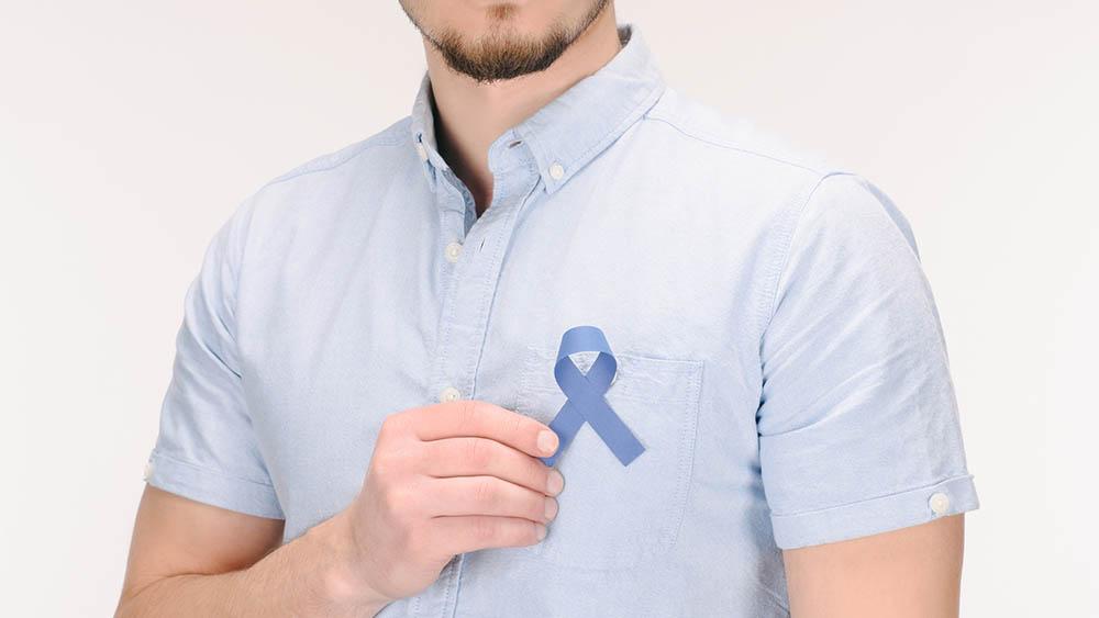 Homem segurando um laço azul, símbolo do Novembro Azul, na altura do peito.