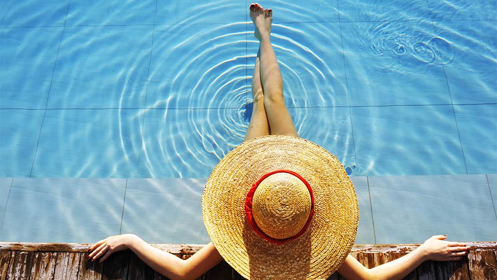 Vista de cima de uma mulher com chapéu sentada na borda de uma piscina.