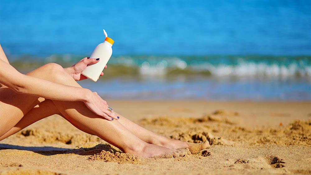 Mulher passando protetor solar nas pernas.