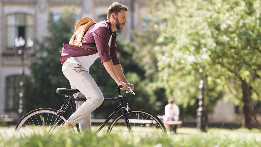 Perfil de homem andando de bicicleta em uma rua arborizada.