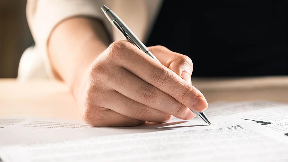 Close em uma mão de mulher assinando um papel.