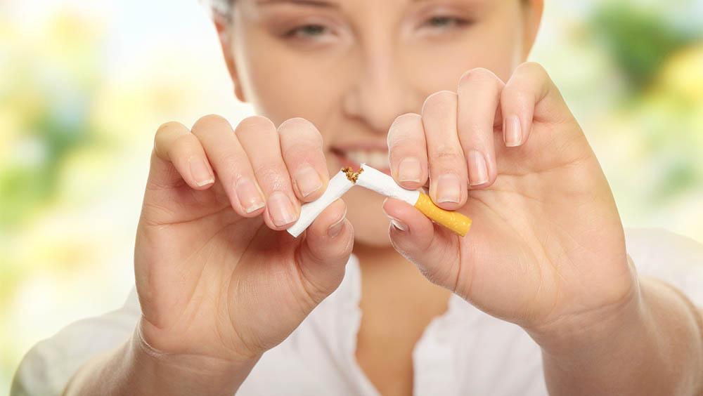 Mulher desfocada quebrando um cigarro ao meio.