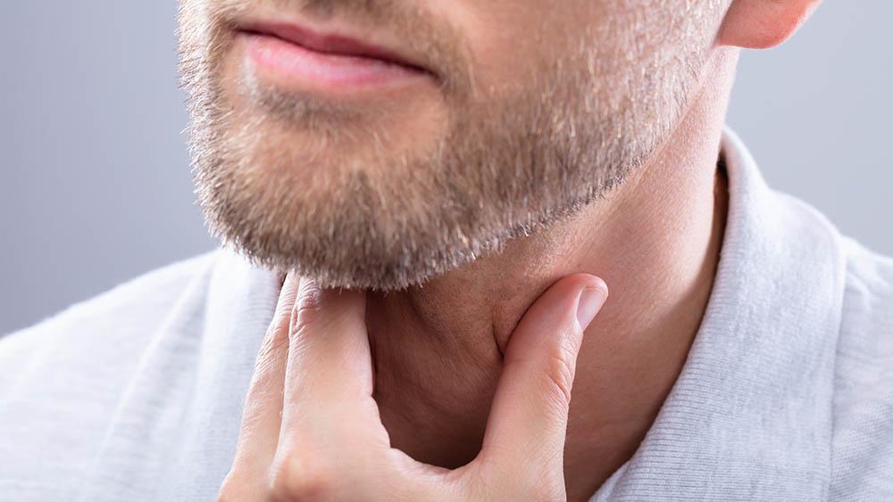 Close de homem apalpando a própria garganta em sinal de dor ou incômodo.