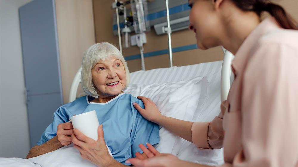 Mulher mais velha sorrindo sentada em cama de hospital com mulher conversando ao lado.